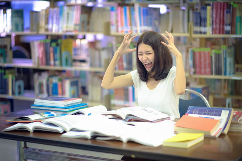 Image: Distressed student surrounded by books